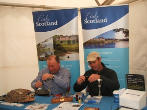 Paul Procter and Paul Little tying flies on the FishPal stand at the BFFI